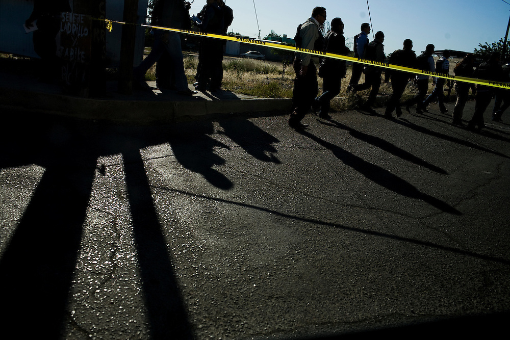 Colleagues of a fallen police officer walk to the scene of his murder in Ciudad Juarez, Chihuahua Mexico on May 3, 2010. ..