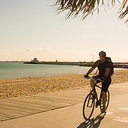 Man cycling along St Kilda Beach in Melbourne, Australia with St Kilda Pier in background.