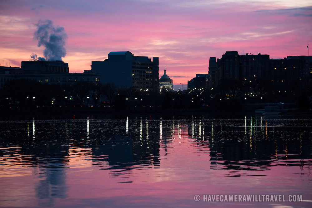 Washington DC--Pink skies before dawn behind a silhouette of buildings on the eastern side of the Tidal Basin in Washington DC. In the center of frame, in the distance, is the US Capitol Dome.