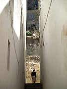 A traveler walks through one of the many white-washed alleys in Arcos de la Frontera, Spain.