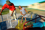 """Five-year-old Mya Cooks, center, lets her spirit go free whle enjoying a spin on the merry-go-round, as her dad """"T"""" holds on for dear life at Derbyshire Park. Cook's sister Tristin, 9, hangs off the edge."""