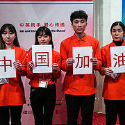 Chinese volunteer (Together we fight against the virus) holding with Chinese characters(中国加油 - Go China!) at China-UK United We Stand together to fights the #Covid19 at Guildhall, on 28th February 2020, London, UK.