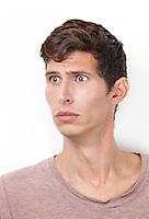 Shocked young man looking away against white background