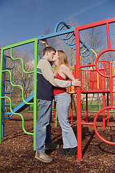Young teenage couple kissing in children's playground,