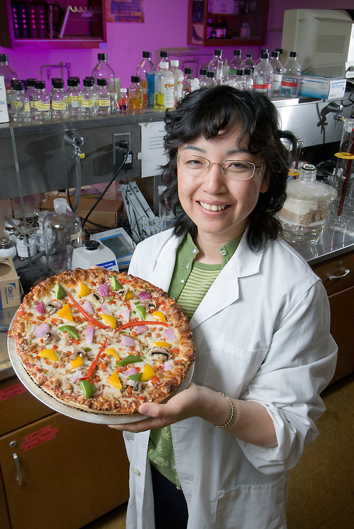 Woman holding a pizza in a food lab