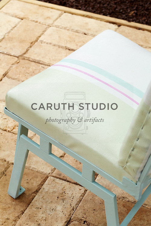 Painted upholstery on midcentury patio chair in pergola-covered patio