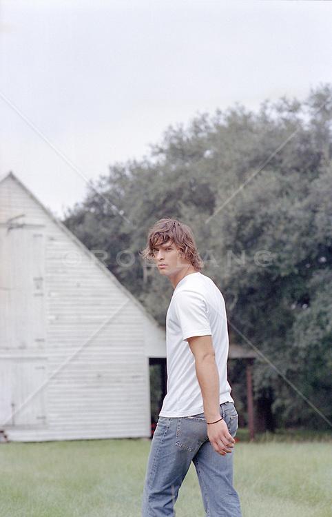 sexy man walking by a rustic barn