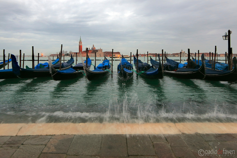 Gondolas at Riva degli Schiavoni in Venice, Itayl, waving in the rising tide (Acqua Alta) that will soon flood the sidewalk