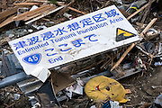 A sign indicating the end of a tsunami  inundation area lies among the debris after the mega-tsunami in Minamisanriku, Miyagi Prefecture, Japan on 14 March, 2011. Photographer: Robert Gilhooly
