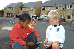 Three children playing with trading cards on their Housing Association estate; Halifax; Yorkshire UK