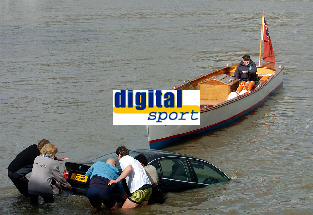 Photo: Daniel Hambury.<br />Varsity Boat Race Preview Day. 29/03/2006.<br />People try to rescue a car caught by the high tide.