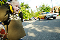 Nate Smith, 3, makes sure his hearing protection is on tight before the onslaught of roaring classic cars roll by his vantage point at Seventh Street and Lakeside Avenue.