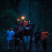 Camp counselor Jeff Marano, 23, of Georgia, leads junior campers thorough the woods before participating in a final campfire at Interlochen Center for the Arts, Michigan.