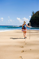 Female hiker walking toward the surf on  Hanakapiai Beach.  The Na Pali Coast of Kauai, Hawaii.