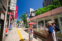 A woman dressed in bright kimono with traditional umbrella walks along a modern Sapporo street.