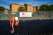 A train travels past an array of solar panels being cleaned next to the line near Aldershot Railway Station.  This innovative project is the first in the UK to power the railway with electricity generated from solar power and, if successful, could see many Network Rail sites across the country adapting this sustainable energy approach. Riding Sunbeams is a social enterprise, run by 10:10 Climate Action. Built with Community Energy South and partnered with Network Rail and The Department for Transport and by InnovateUK.  Aldershot, Hampshire, United Kingdom. Riding Sunbeams is a world leading project to connect solar panels directly into electrified rail routes to power the trains. Direct supply of solar power to rail traction systems has never been done. But it has huge potential - from metros, trams and railways in the UK and around the world.<br /> (photo by Andy Aitchison / 1010 Climate Action)