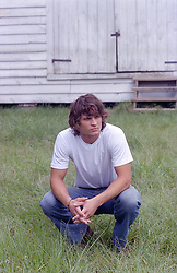 good looking man squatting in grass by a barn