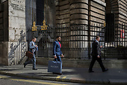 City Businessmen and sunlit railings of St. Mary Woolnoth church on Lombard Street, on 10th May 2017, in the City of London, England.