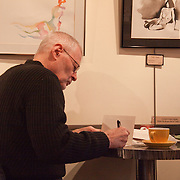 Man writing in coffeehouse, Local Color, Pike Place Market, Seattle, Washington