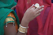 extreme close up of an Indian girl in traditional dress with cymbals in her hand