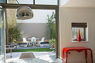 View from inside to contemporary table and chairs in enclosed courtyard garden outside, astroturf