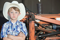 Portrait of a boy wearing cowboy hat while standing with arms crossed against machine