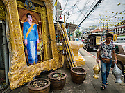 10 AUGUST 2016 - BANGKOK, THAILAND: A man walks past a portrait of Queen Sirikit of Thailand. Thais are preparing for the Queen's birthday. Queen Sirikit of Thailand, was born Mom Rajawongse Sirikit Kitiyakara on 12 August 1932. She married  Bhumibol Adulyadej, King of Thailand (Rama IX) in 1950. He is the longest serving monarch in the world and she is longest serving consort of a monarch. Her birthday, like the King's Birthday (which falls on Dec. 5),  is a national holiday in Thailand. Her birthday, August 12, is also celebrated as Mothers' Day in Thailand. Thais hang portraits of Queen Sirikit in their homes and fly her royal flag on her birthday.        PHOTO BY JACK KURTZ