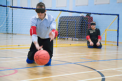 Centre team player throwing ball during a Goalball game; a threeaside game developed for the visually impaired and played on a volleyball court, A specially adapted ball containing an internal bell is used,
