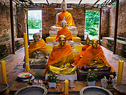 17 JULY 2017 - INTHA PRAMUN, ANG THONG, THAILAND: Statues of the Buddha and revered monks in a historic prayer hall at Wat Khun Inthapramun. Wat Khun Inthapramun houses the largest and longest reclining Buddha in Thailand. The statue of the reclining Buddha is more than 50 meters long. The temple is located in the middle of rice fields, in the southern part of the Pho Thong district. The temple was built during the Sukhothai era, is revered in Thai history and late King Bhumibol Adulyadej (Rama IX) visited twice, in 1973 and 1975.    PHOTO BY JACK KURTZ