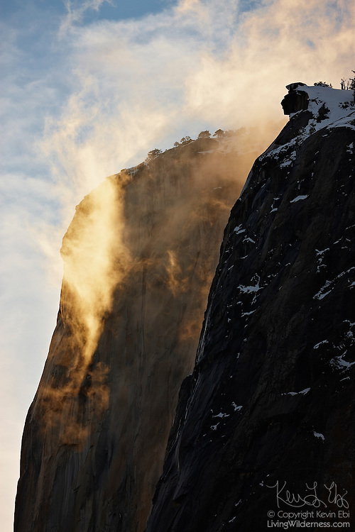 Thin clouds, lit by the setting sun, hang at the summit of El Capitan in Yosemite National Park, California.
