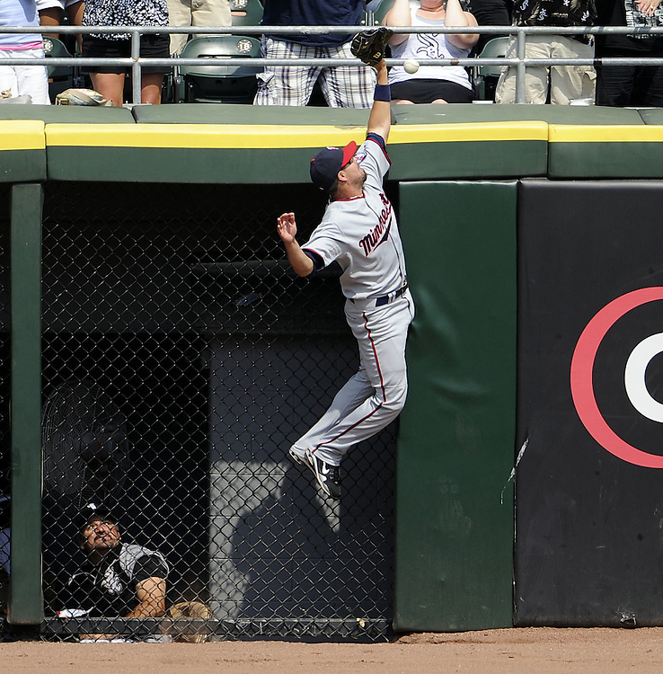CHICAGO - JULY 09:  Jason Repko #18 of the Minnesota Twins leaps but cannot catch the home run hit by Alexei Ramirez #10 of the Chicago White Sox in the first inning on July 9, 2011 at U.S. Cellular Field in Chicago, Illinois.  The White Sox defeated the Twins 4-3.  (Photo by Ron Vesely)  Subject: Jason Repko;Alexei Ramirez