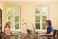 Young couple using computers across table in living room