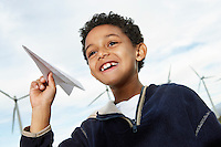 Boy (7-9) playing with paper plane at wind farm
