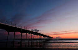 © Licensed to London News Pictures. 28/04/2016. SALTBURN BY THE SEA, UK.  <br /> Purple and orange clouds fill the sky as the sun rises over the beach and pier at Saltburn by the Sea.  <br /> Photo credit: Ian Forsyth/LNP