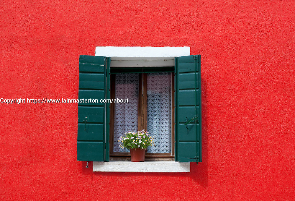 Window frame in colourful red house in village of Burano near Venice in Italy