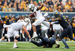 Oct 28, 2017; Morgantown, WV, USA; Oklahoma State Cowboys running back J.D. King (27) runs the ball and jumps over West Virginia Mountaineers linebacker David Long Jr. (11) during the first quarter at Milan Puskar Stadium. Mandatory Credit: Ben Queen-USA TODAY Sports