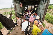 01 JULY 2006 - PHNOM PENH, CAMBODIA: Passengers sit on the floor and in hammocks they bring with them when they ride in the boxcar on the Phnom Penh - Battambang train. Passengers sit wherever they can find space - in the few passenger cars on the train, the flat cars and the box cars. While much of Cambodia's infrastructure has been rebuilt since the wars which tore the country apart in the late 1980s, the train system is still in disrepair. There is now only one passenger train in the country. It runs from Phnom Penh to the provincial capitol Battambang and it runs only one day a week. It takes 12 hours to complete the 190 mile journey.  Photo by Jack Kurtz / ZUMA Press