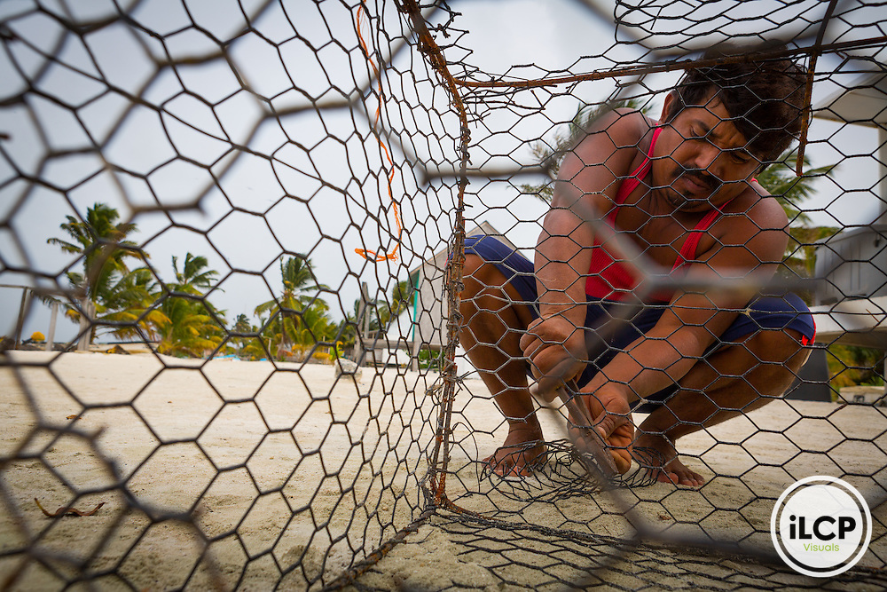 A fisherman building a crab pot in Punta Herrero, a small, remote fishing camp in the Sian Ka'an Biosphere Reserve in southernmost Caribbean Mexico. From a 2014 iLCP (International League of Conservation Photographers) expedition project documenting the people and places of the Mexican section of the Mesoamerican Reef (MAR).