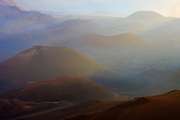 The cinder cones of Maui's Haleakala crater are backlit by the low-angled light of sunrise.