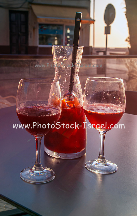 Holiday concept two glasses of Sangria and a pitcher on the Atlantic Coast at sunset