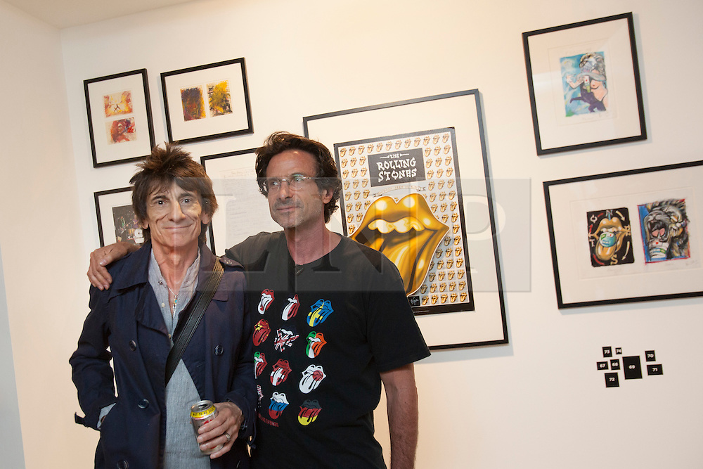 © licensed to London News Pictures. London, UK 13/08/2012. Ronnie Wood (L) and Bernie Chase posing next to The Rolling Stones poster, drawings and paintings at the 'A Major Retrospective Of 50 Years Of Rock And Roll' exhibition in central London.  Photo credit: Tolga Akmen/LNP