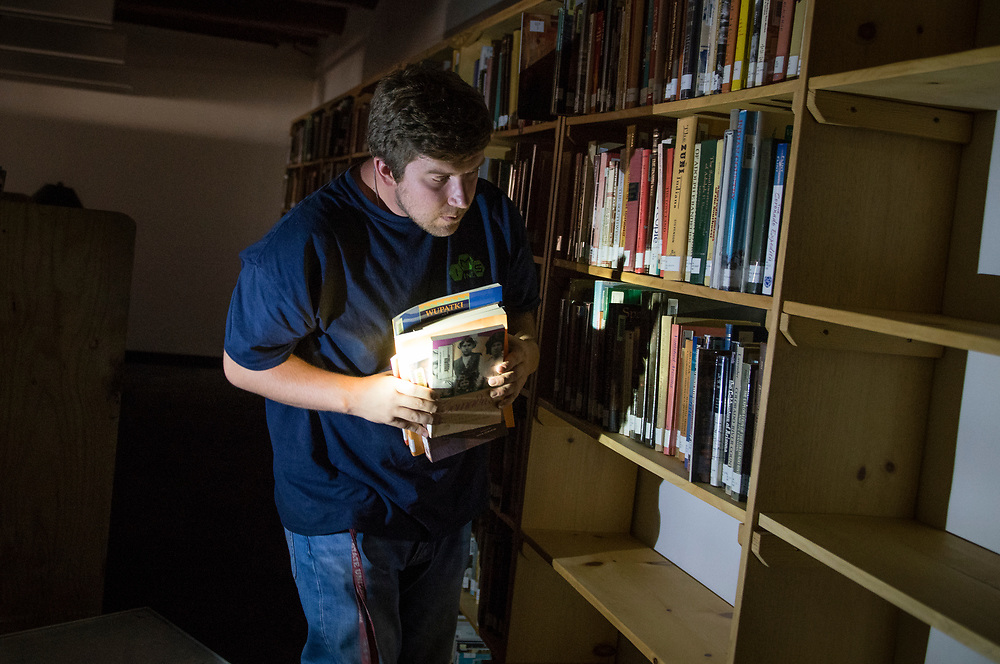 rer062917d/Rio Rancho/June 29, 2017/Albuquerque Journal<br /> The Martha Liebert Public Library in the town of Bernalillo is moving across the street.  Pictured is Samuel Lauer(Cq) shelving books in the new facility under the power of a flashlight because the electricity is in the process of being connected. <br /> Bernalillo, New Mexico Roberto E. Rosales/Albuquerque Journal