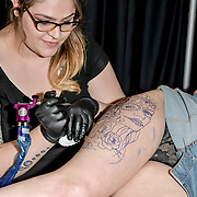 Beth Chloe Tattoos tattoo a client at The Great British Tattoo Show, on 26 May 2019, London, UK.