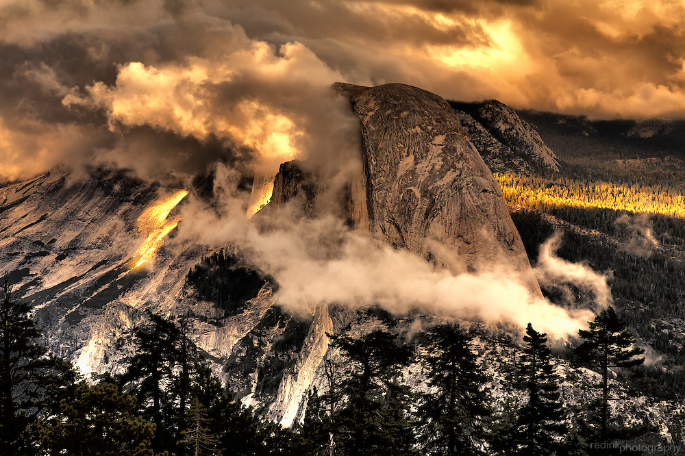 Storm clouds rush through the Yosemite Valley Floor and ring Half Dome. The late afternoon sun breaks through providing color and light through the clouds. As seen from Sentinel Dome. Yosemite National Park, Sierra Nevada Mountains, California.