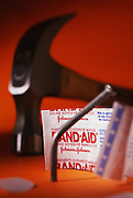 Bandaid wrapper with hammer and bent nail on orange background
