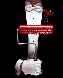 man in formal tuxedo with dripping red paint roller red rose