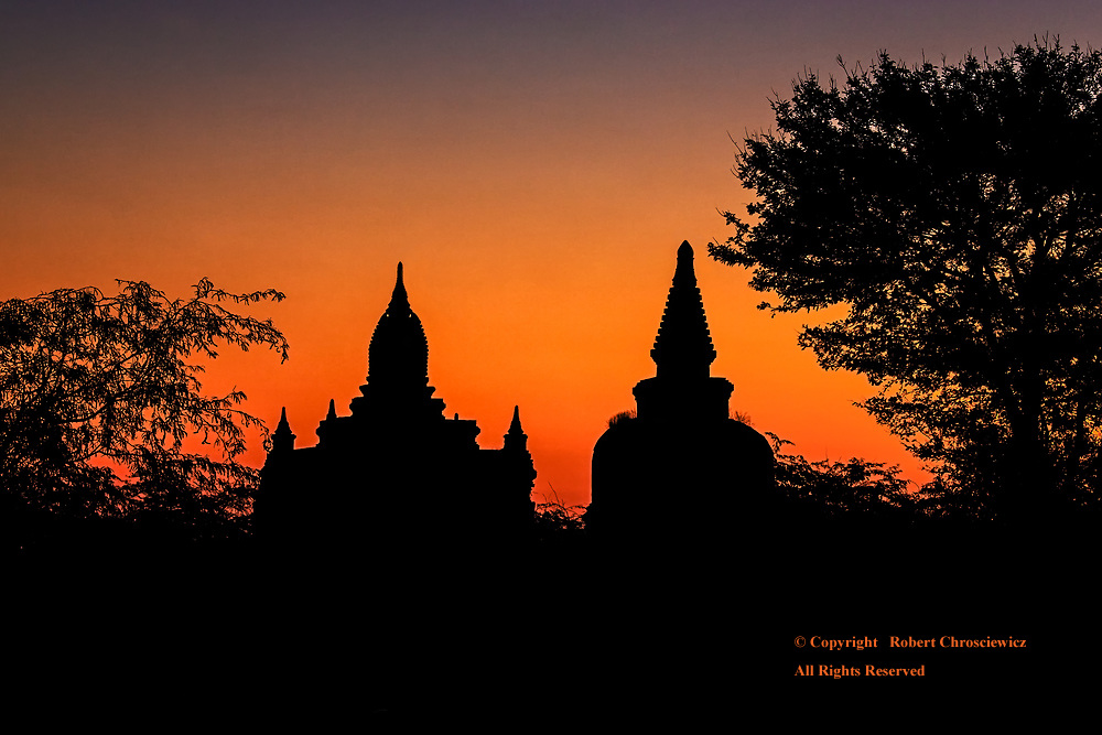 Ancient Silhouette: The silhouettes of ancient Buddhist temples, within a forested landscape, are captured during a glorious sunrise, Bagan Myanmar.