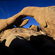 The long span of Arch Rock frames a brilliantblue sky in Joshua Tree National Park in the Mojave Desert..Also sometimes called Ryan Arch.