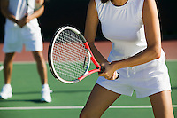 Mixed doubles tennis players on court focus on woman mid section