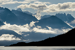 Clouds swirl around unnamed mountain peaks near Sinclair Mountain in the Kakuhan Range bask in this view seen from Picture Point in Haines, Alaska.